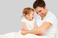 Happy family father and baby  daughter playing in bed Royalty Free Stock Image