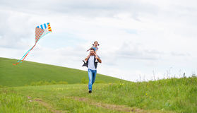 Happy family father and baby daughter run with  kite on meadow Stock Photography