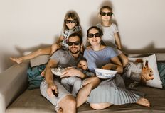 Happy family father with baby on his arms, mother and two daughters in the special glasses watching tv and eating royalty free stock image