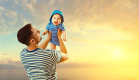Happy family father and baby son on beach by sea at sunset Royalty Free Stock Image