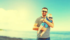 Happy family father and baby son on beach by sea at sunset Stock Photos