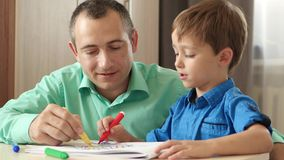 Happy family. Father and child. Dad helps his son draw with colored pencils. Relationships and fatherhood. Education. stock video
