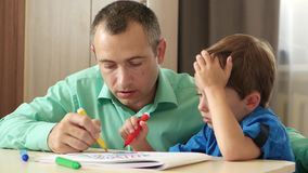 Happy family. Father and child. Dad spends time with his son imagining and painting a picture with colored markers. stock footage