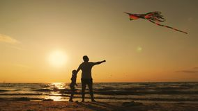 Happy family father and child daughter launch a kite on beach at sunset. Funny family time. Concept of friendly family stock footage