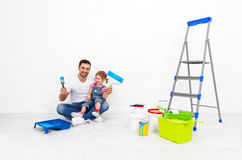 Happy family father and child daughter making repairs, paint wal Stock Photos