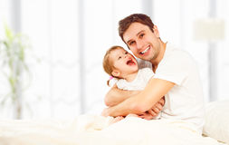 Happy family father and child  daughter playing in bed Stock Image