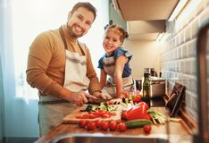 Happy family father with child daughter preparing vegetable salad royalty free stock image