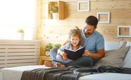 Happy family father and daughter reading book in bed. Happy family father and child daughter reading book in bed