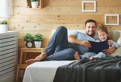 Happy family father and daughter reading book in bed Stock Photography