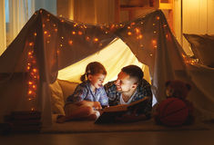 Happy family father and child daughter reading a book  in  tent. Happy family father and child daughter  reading a book with a flashlight in a tent at home Stock Photography