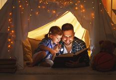 Happy family father and child daughter reading a book in tent. Happy family father and child daughter reading a book with a flashlight in a tent at home stock images
