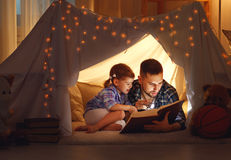 Happy family father and child daughter reading a book in tent. Happy family father and child daughter reading a book with a flashlight in a tent at home Royalty Free Stock Image