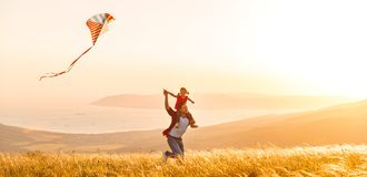 Happy family father and child daughter run with  kite on meadow. Happy family father and child daughter run with a kite on meadow Stock Photo