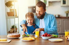 Happy family father with child  feeds his   daughter in kitchen with Breakfast stock photography
