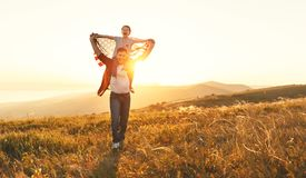 Happy family father and child with flag of united states enjoyi. Ng sunset on nature stock photography