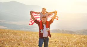 Happy family father and child  with flag of united states enjoyi. Happy family father and child with flag of united states enjoying sunset on nature Royalty Free Stock Image