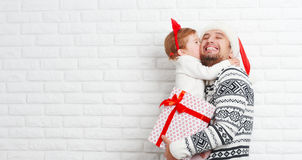 Happy family father and child with gift in Christmas kiss Stock Images