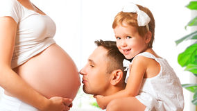 Happy family. father and child kissing belly of mother pregnant Royalty Free Stock Images