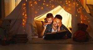 Happy family father and child  reading  book  in  tent at home. Happy family father and child daughter  reading a book with a flashlight in a tent at home Royalty Free Stock Photo