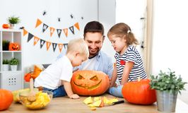 Happy family father and children cut pumpkin for   halloween Royalty Free Stock Photo