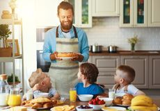 Happy family father with children feeds his sons and daughter in kitchen with Breakfast. Happy family father with many children feeds his sons and daughter in stock photo