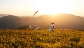 Happy family father and children launch kite on nature at sunset stock photography