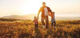 Happy family father and children in nature at sunset stock images