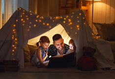 Happy family father and children reading a book  in  tent at hom. Happy family father and children reading a book with a flashlight in a tent at home Stock Photo
