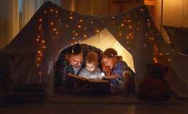 Happy family father and children reading a book  in  tent at hom. Happy family father and children reading a book with a flashlight in a tent at home Stock Photos