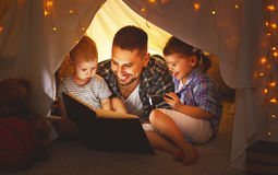 Happy family father and children reading a book in tent at hom. Happy family father and children reading a book with a flashlight in a tent at home