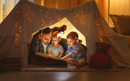 Happy family father and children reading a book  in  tent at hom. Happy family father and children reading a book with a flashlight in a tent at home Royalty Free Stock Photography