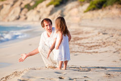 Happy family father and daughter on beach having fun Stock Images
