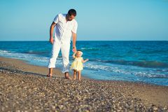Happy family, father with daughter on the beach, learn to walk. stock photo