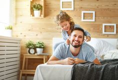 Happy family father and   daughter laughing and playing in bed Stock Photography