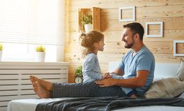 Happy family father and   daughter reading book in bed Royalty Free Stock Photos