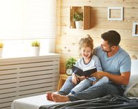 Happy family father and daughter reading book in bed Stock Images