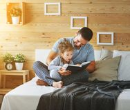 Happy family father and daughter reading book in bed Royalty Free Stock Photo