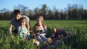 Happy family, father and daughters are sitting close together and enjoy the time at the picnic on the green beautiful. Meadow on a sunny day. Outdoors stock video footage