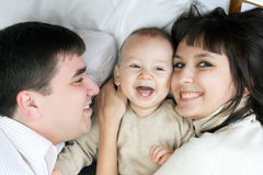 Happy family - father, mother and baby. Happy family home: father, mother and baby lying on the floor and playing stock photo