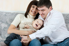 Happy family - father, mother and baby Stock Images