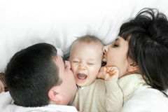 Happy family - father, mother and baby. Happy family home: father, mother and baby lying on the floor and playing stock image