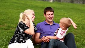 Happy family: father, mother and baby playing at grass stock video