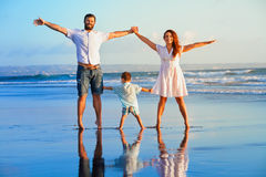 Happy family - father, mother, baby on summer beach vacation Stock Photos