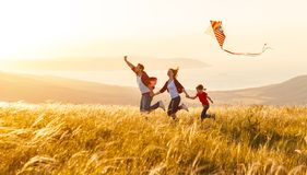 Happy family father,  mother and child daughter launch a kite on Stock Photo