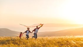 Happy family father, mother and child daughter launch a kite on. Nature at sunset royalty free stock photo