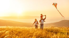 Happy family father of mother and child daughter launch a kite o. N nature at sunset Stock Photos