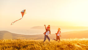 Happy family father of mother and child daughter launch a kite o. N nature at sunset stock images
