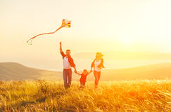 Happy family father of mother and child daughter launch a kite o. N nature at sunset royalty free stock photos