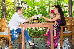 Happy family of father, mother and child drinking tea at the table on a summer day. Portrait parents and kid on nature. Positive h. Happy family of father royalty free stock photo