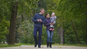 Happy family: Father, Mother and child - little girl in autumn park: walking near trees. Telephoto shot stock video